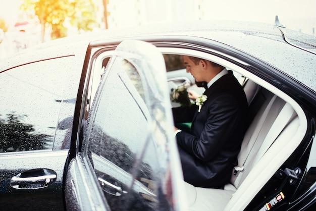 Szczęśliwa piękna panna młoda, siedzi w ślubnym samochodzie z bukietem