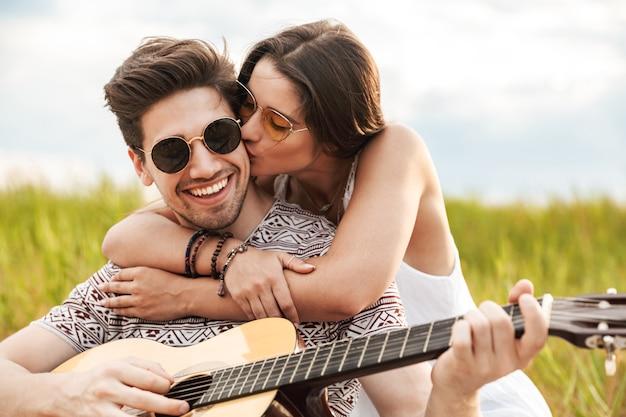 Szczęśliwa piękna para siedzi razem w parku, gra na gitarze, odpoczywa