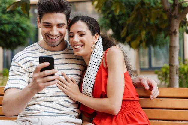 Szczęśliwa piękna para uśmiecha się i używa telefonu komórkowego siedząc na ławce na ulicy miasta