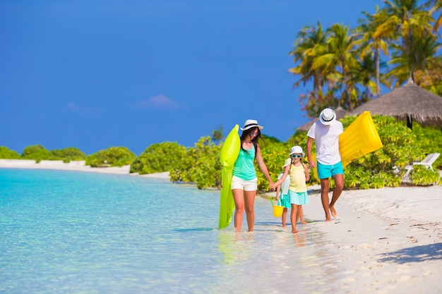 Szczęśliwa piękna rodzina na białej plaży z dmuchanymi materacami