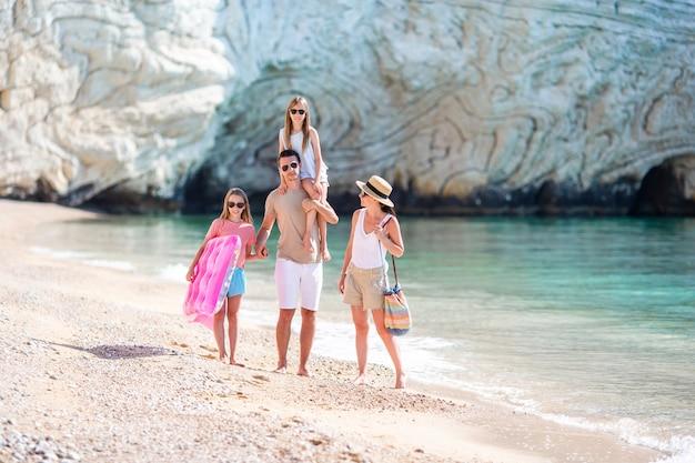 Szczęśliwa piękna rodzina na biel plaży ma zabawę wpólnie