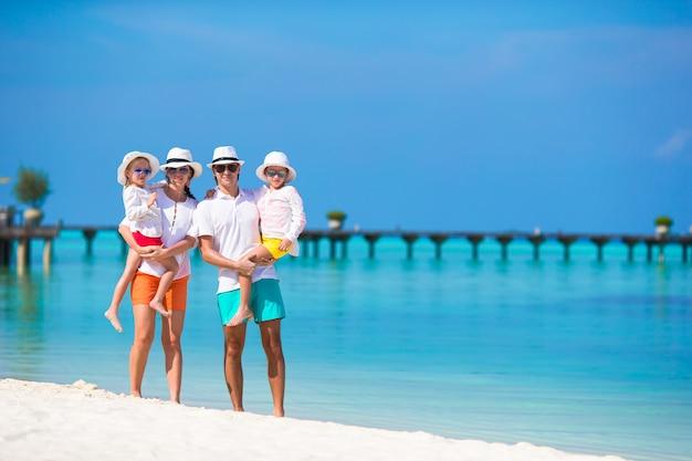 Szczęśliwa piękna rodzina na biel plaży podczas wakacje