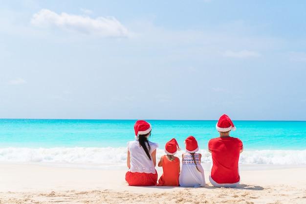 Szczęśliwa piękna rodzina w czerwonych santa kapeluszach na tropikalnej plaży świętuje boże narodzenia