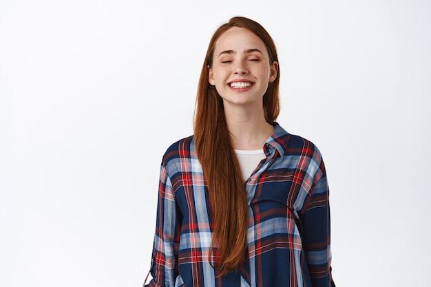 Szczęśliwa piękna ruda dziewczyna z długimi naturalnymi włosami uśmiecha się z zamkniętymi oczami