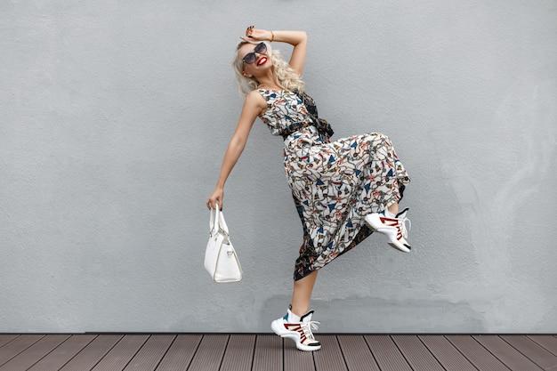 Szczęśliwa piękna śmieszna młoda kobieta z okularami przeciwsłonecznymi z białą torbą w modnej sukience z wzorem i butami skaczącymi w pobliżu szarej ściany. zakupy lifestyle