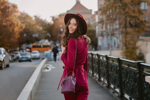 Szczęśliwa piękna stylowa kobieta w fioletowym garniturze spaceru ulicą miasta, trend w modzie wiosna lato jesień sezon w kapeluszu, trzymając torebkę