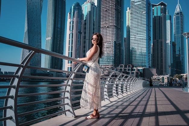 Szczęśliwa piękna turystyczna kobieta w dubaj marina