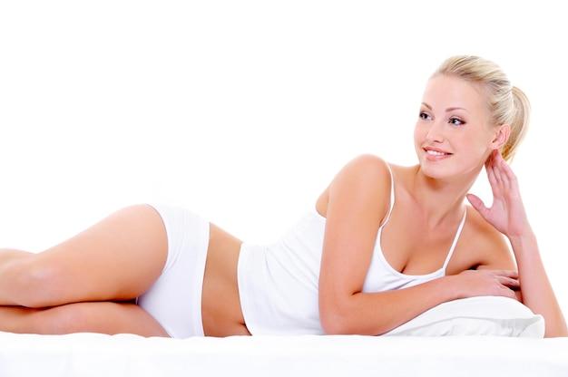 Szczęśliwa piękna uśmiechnięta kobieta z sexy ciało leżąc w bieliźnie na białym łóżku