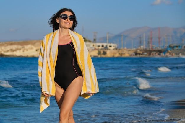Szczęśliwa piękna zdrowa dojrzała kobieta w stroju kąpielowym z ręcznikiem spacerowym wzdłuż morza. fale morskie, zachód słońca, piękne malownicze tło