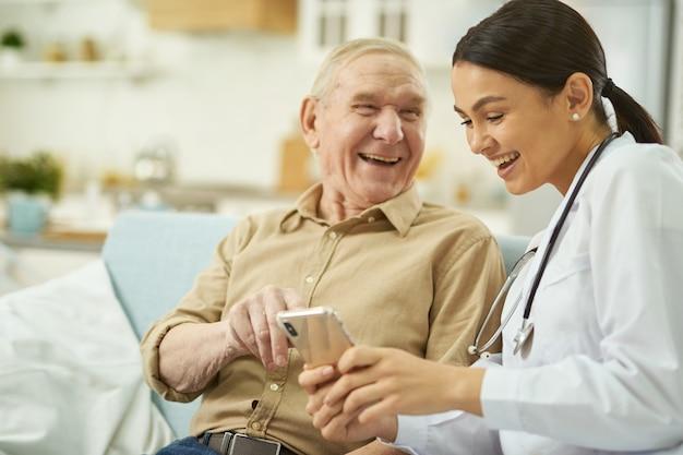 Szczęśliwa pielęgniarka i senior siedzący na kanapie i korzystający z telefonu komórkowego