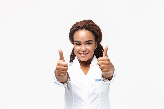 Szczęśliwa pielęgniarka uśmiechająca się i pokazująca kciuki do góry na białym tle na białej ścianie