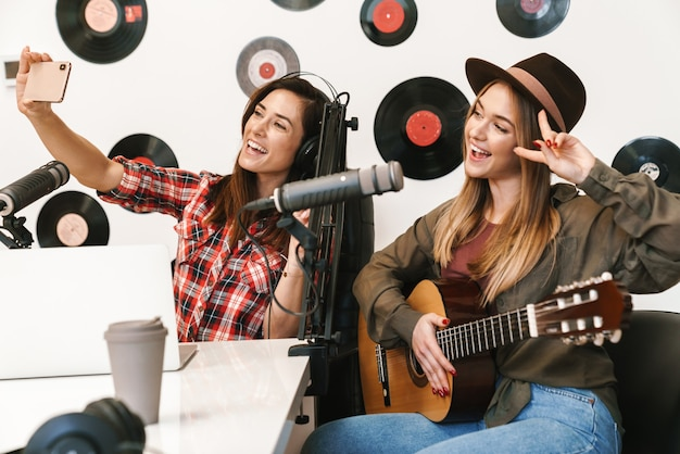 Szczęśliwa piosenkarka występująca w programie radiowym podczas nagrywania podcastu do programu online, grająca na gitarze, robiąca selfie z gospodarzem