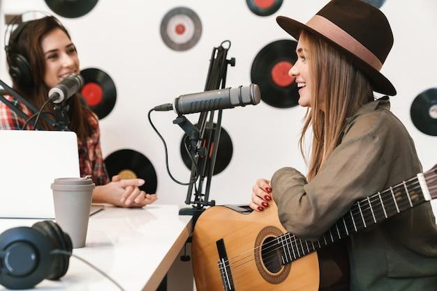 Szczęśliwa piosenkarka występująca w programie radiowym podczas nagrywania podcastu do programu online, grająca na gitarze