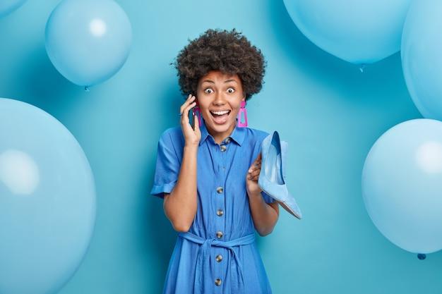 Szczęśliwa podekscytowana afroamerykańska dama nosi niebieską sukienkę, w której znajdują się buty na wysokim obcasie sukienki na specjalne okazje