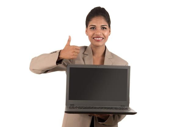 Szczęśliwa podekscytowana biznesowa kobieta trzyma laptop i pokazuje kciuki do góry na białym tle