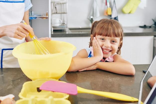 Szczęśliwa podekscytowana dziewczynka siedzi przy kuchennym blacie, gdy jej matka trzepocze jajka w dużej plastikowej misce