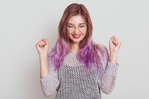 Szczęśliwa podekscytowana kobieta świętuje zwycięstwo zaciskając pięści i uśmiechając się zębami, ciesząc się, że osiąga cele