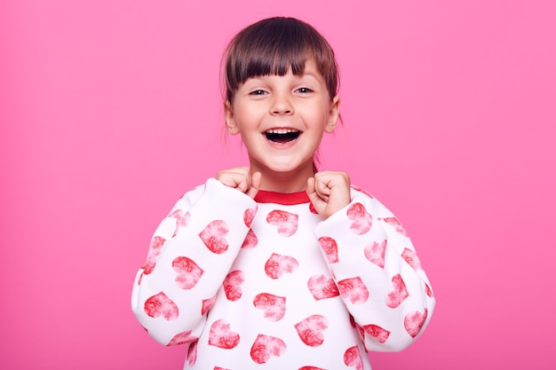 Szczęśliwa podekscytowana mała dziewczynka zaciskająca pięści, świętująca swój sukces, patrząc na kamerę z podekscytowanymi emocjami, odizolowana na różowej ścianie.