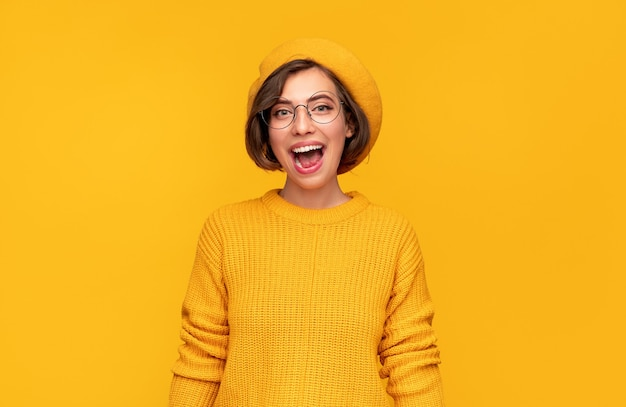 Szczęśliwa podekscytowana młoda brunetka w okularach na sobie żółty sweter z dzianiny i kapelusz patrząc na kamerę z otwartymi ustami, ciesząc się dobrą wiadomością na żółtym tle