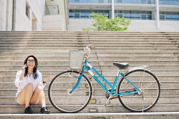Szczęśliwa podekscytowana młoda chinka siedzi obok swojego roweru i rozmawia przez telefon z przyjacielem