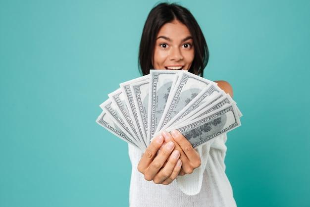 Szczęśliwa podekscytowana młoda kobieta trzyma wiązkę stanów zjednoczonych dolary
