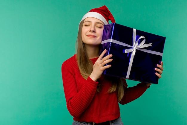 Szczęśliwa podekscytowana młoda kobieta w kapeluszu świętego mikołaja z pudełkiem na niebieskim tle - image