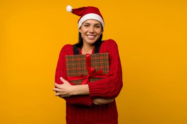 Szczęśliwa podekscytowana młoda kobieta w kapeluszu świętego mikołaja z pudełkiem na żółtym tle - image