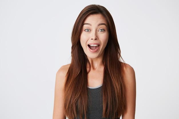 Szczęśliwa podekscytowana młoda kobieta z długimi włosami stoi z otwartymi ustami i wygląda na zaskoczonego