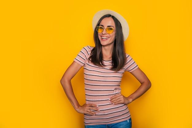 Szczęśliwa podekscytowana piękna turystka kobieta w kapeluszu i okularach przeciwsłonecznych pozuje na żółtym tle i dobrze się bawi