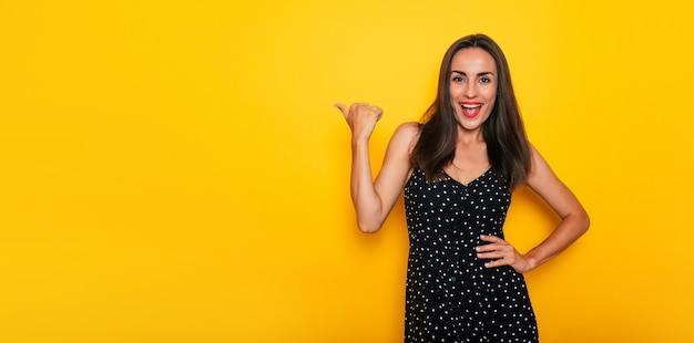 Szczęśliwa podekscytowana przepiękna uśmiechnięta brunetka w czarnej letniej sukience pozuje na białym tle na żółtym tle i wskazuje daleko
