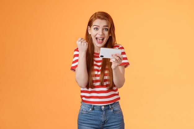 Szczęśliwa podekscytowana rudowłosa kobieta przechodzi poziom jak niesamowita gra wynik cel trzymaj smartfon poziomo fi...