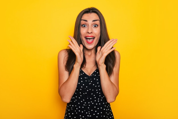 Szczęśliwa podekscytowana wspaniała uśmiechnięta brunetka w czarnej letniej sukience pozuje na białym tle na żółtym tle i dobrze się bawi