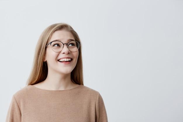 Szczęśliwa podekscytowana zdziwiona modelka z prostymi blond włosami w okularach, będąc z czegoś zadowolona, nie może uwierzyć w swój sukces, cieszę się z pochwały, pozuje na szarym tle studia