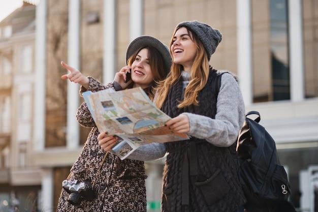 Szczęśliwa podróż razem dwóch modnych kobiet w słonecznym centrum miasta. młode radosne kobiety wyrażające pozytywne nastawienie, posługujące się mapą, wakacje z torbami, wesołe emocje, dobry dzień.