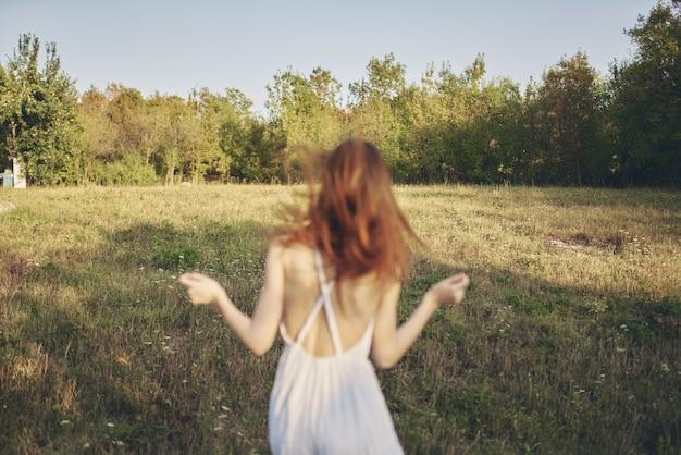 Szczęśliwa podróż w białej sukience biegającej po trawie w przyrodzie.