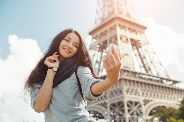 Szczęśliwa podróżnicza kobieta robi sobie śmieszne selfie swoim telefonem komórkowym w pobliżu wieży eiffla w paryżu
