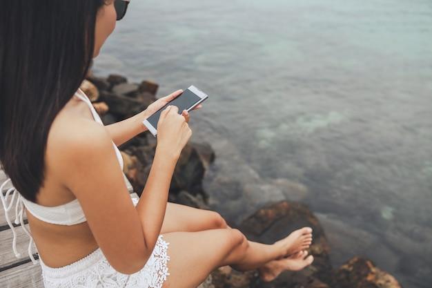 Szczęśliwa podróżniczka azjatycka kobieta korzystająca z telefonu komórkowego i relaksująca się w drewnianym moście na plaży