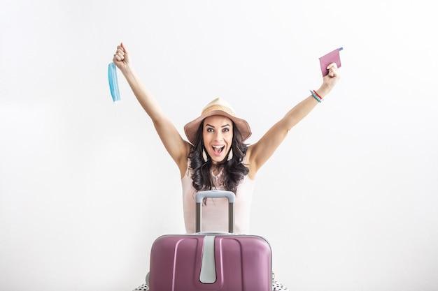 Szczęśliwa podróżniczka stoi przed swoją walizką, z podniesionymi rękami, aby ograniczyć ograniczenia, trzymając w jednej ręce paszport, a w drugiej maskę na twarz.
