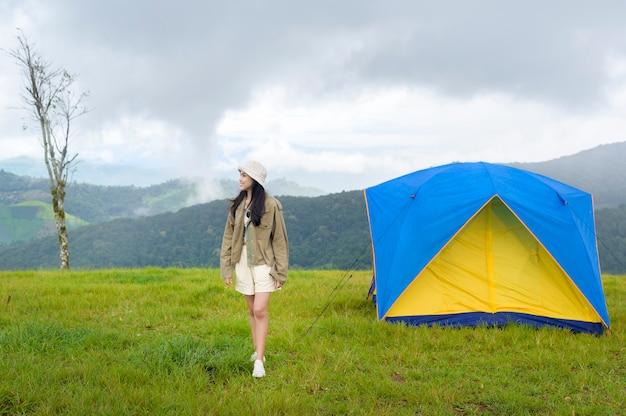 Szczęśliwa podróżująca kobieta korzystająca i relaksująca w pobliżu namiotu obozowego