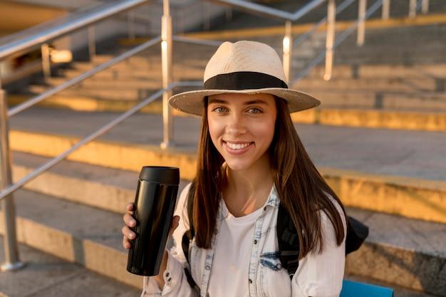 Szczęśliwa podróżująca kobieta z plecakiem i kapeluszem trzymając termos