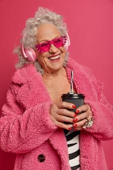 Szczęśliwa pomarszczona starsza kobieta pije kawę na wynos, nosi słuchawki i słucha muzyki