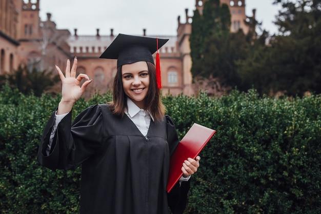Szczęśliwa pomyślna uśmiechnięta kobieta, absolwent uniwersytetu; portret kobiety z dyplomem lub college'u z dyplomem ukończenia studiów