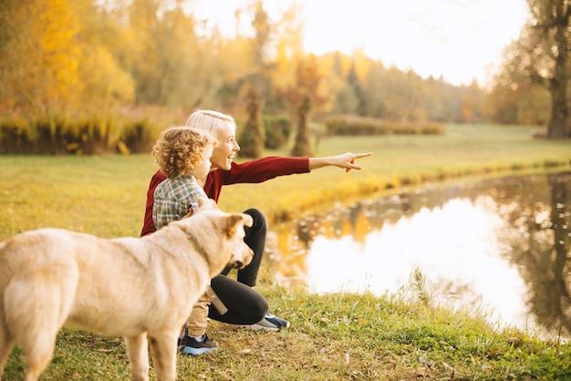 Szczęśliwa potomstwo matka ma pięknego czas z jej dzieciakiem plenerowym w naturze i ma spacer z psem
