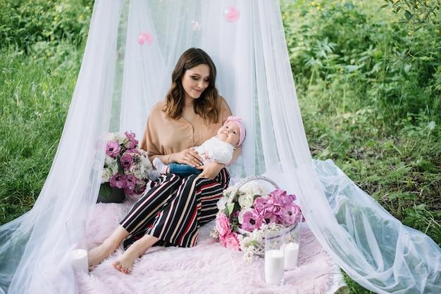 Szczęśliwa potomstwo matka z małą śliczną dziewczyny córką w ogródzie