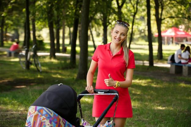 Szczęśliwa potomstwo matka z spacerowiczem w lato parku