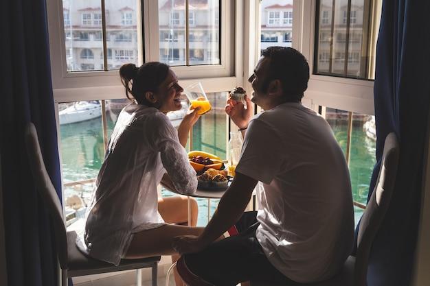 Szczęśliwa potomstwo para cieszy się śniadanie na tarasie