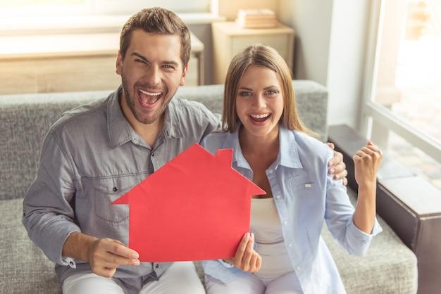 Szczęśliwa potomstwo para trzyma papierowego dom
