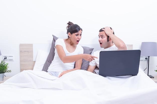 Szczęśliwa potomstwo para używa laptop w łóżku w domu