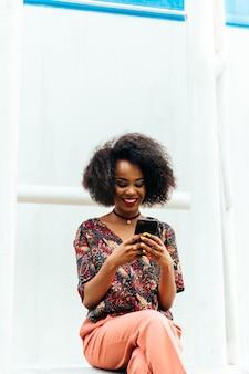 Szczęśliwa powabna afroamerykańska kobieta, patrzeje smartphone ekran, ono uśmiecha się radośnie