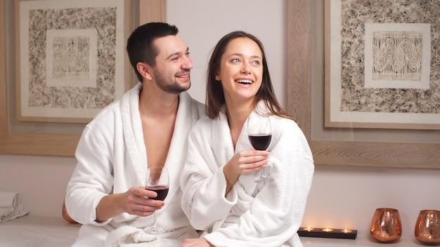 Szczęśliwa powabna para pije wino i śmia się w nowożytnym wellness salonie